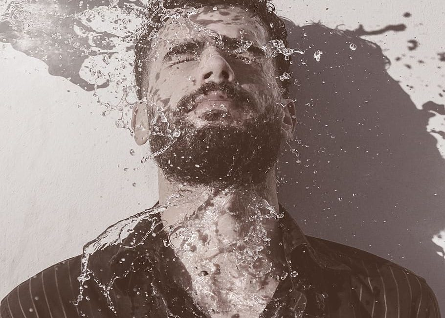 man washing beard with water
